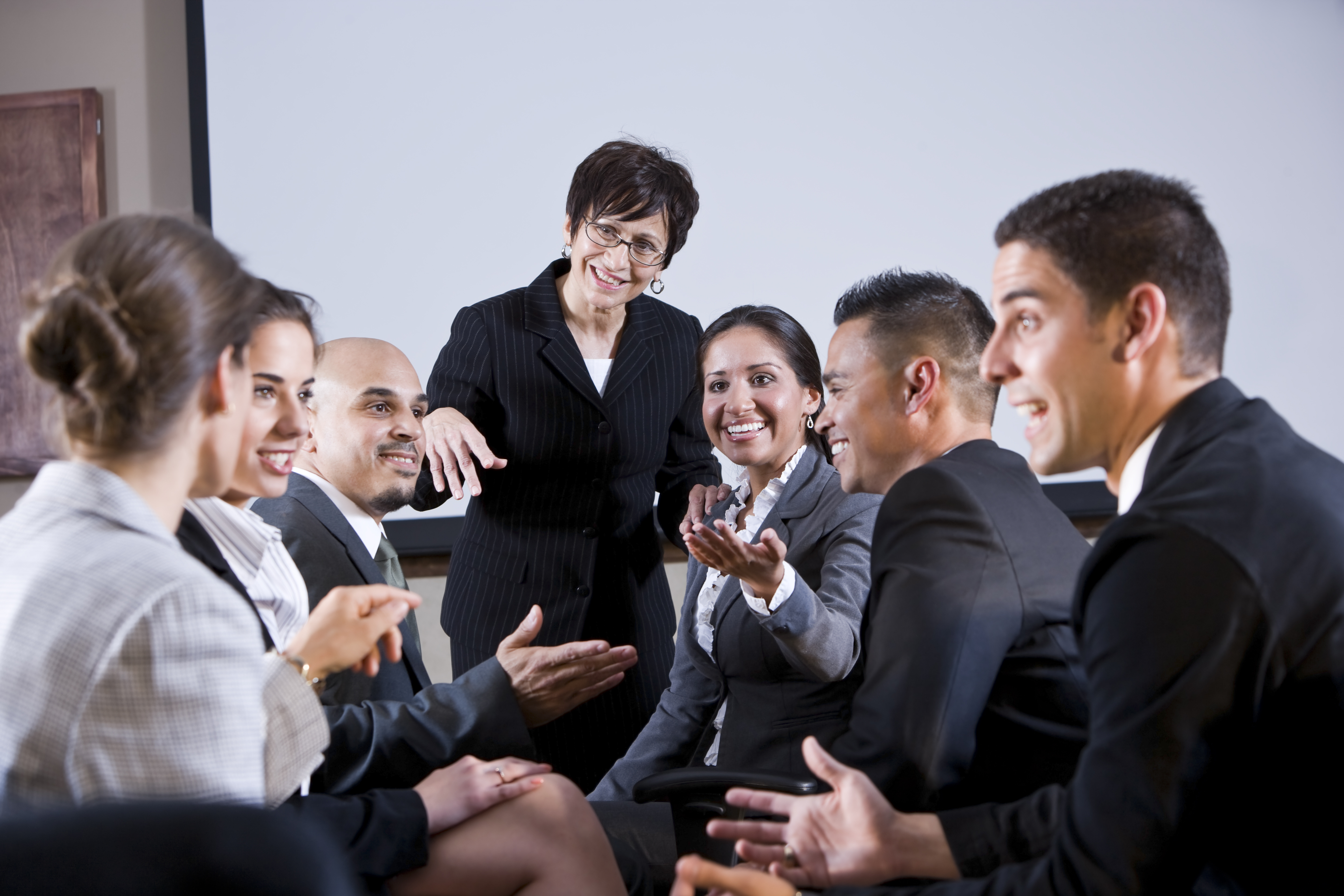Diverse businesspeople conversing, woman at front | Capitol Hill Offices